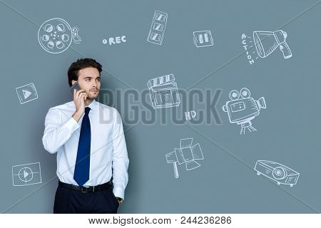 Confident Film Director. Experienced Professional Film Director Looking Serious While Having A Phone