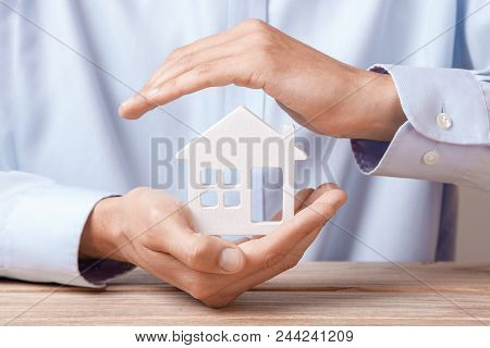 Concept Home Insurance, Protection From Burglary Or Destruction. Man With His Hands Covers The House