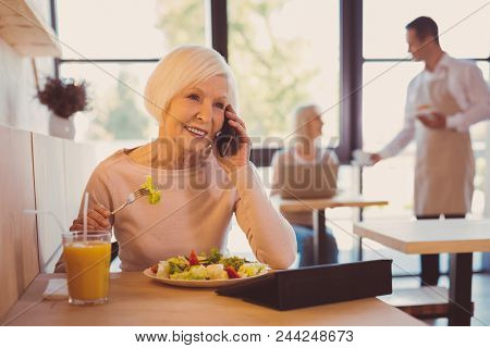 Pleasant Conversation. Charming Elderly Woman Having A Conversation On The Phone With Her Friend Whi