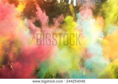 People Dancing During Colorful Holi Festival. Blurred Sunny Sunset Multicolor Background.