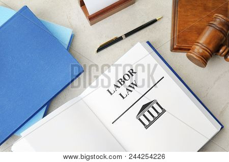Open book with words LABOR LAW and gavel on table, top view poster