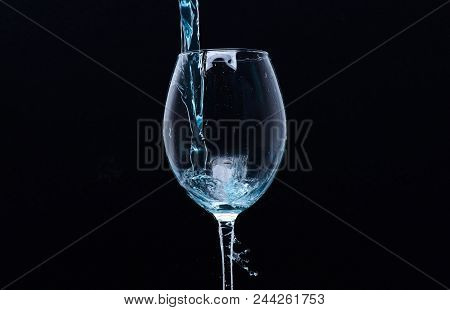 Refreshing Drink Concept. Cocktail With Blue Liquid In Glass. Glass With Blue Water Pouring With Liq