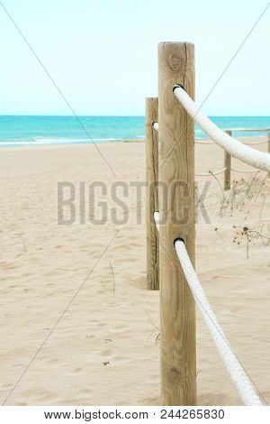 Rope Railing With Wooden Poles On The Beach. Fine White Sand Turquoise Sea Blue Sky. Vacation Relaxa