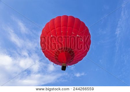 A Red Balloon Is Flying In The Sky. A Balloon With A Basket Lies On The Ground, Equipment For Fillin