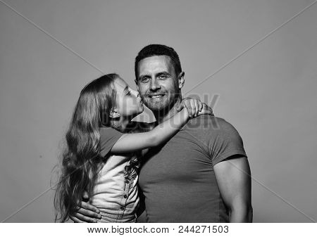 Father And Child With Smiling Faces. Childhood And Fathers Day Concept. Daughter Kisses Her Daddy In