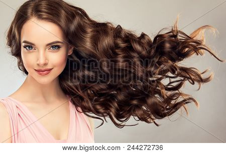 poster of Brunette  girl with long , healthy and   shiny curly hair .  Beautiful  model woman  with wavy hairstyle   .Care and beauty