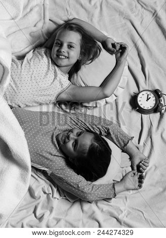 Happy Girls. Schoolgirls In Pink Pajamas Wallow On Colorful Pillows, Top View. Kids With Happy Faces
