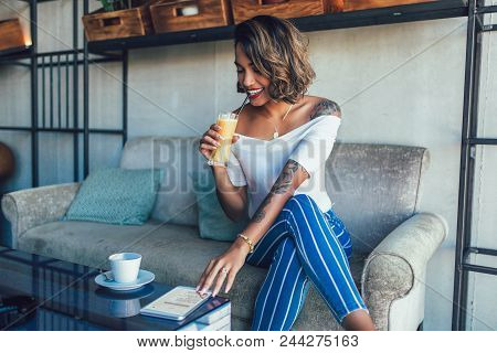 Shot Of Happy Young Black Cuban Woman Drinking Juice In Cafe
