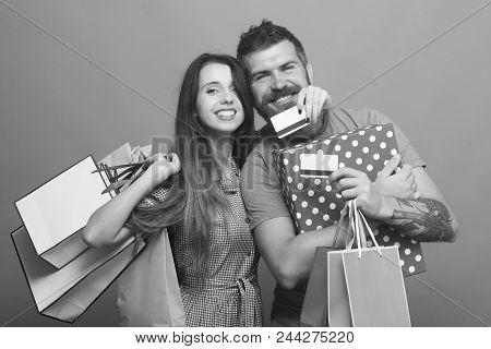 Couple In Love Hugs Holding Shopping Bags And Credit Cards On Blue Background. Guy With Beard And La