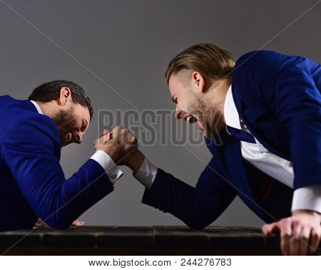Men In Suit Or Businessmen With Tense Faces Compete In Armwrestling On Wooden Table On Dark Backgrou
