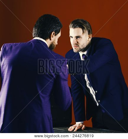 Business Partners With Aggressive Expression At Business Meeting On Burgundy Background. Business Co