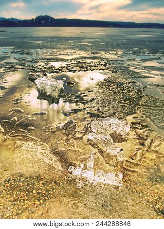 Ice Fragments On Empty Sandy Coast. Frozen Sand On River Coast. Autumn Sunset With Waves On The Yell