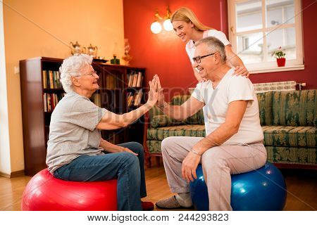 Group Of Senior People Exercise With Physiotherapist In Private Clinic