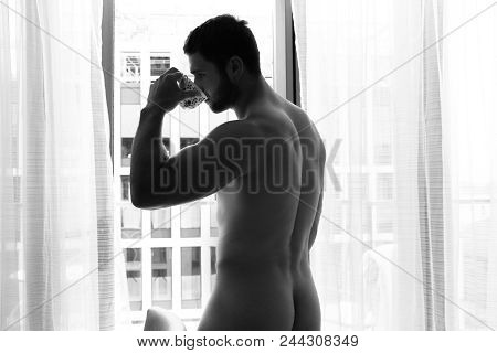 Nude Good Looking Man Shows His Backside And Butt, Bottom, As He Stands In Front Of Curtains Of The