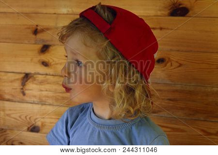 Cropped Shot Of A Cute Little Baby Boy With Curly Hair Wearing Red Hat And Looking To The Side. Chee