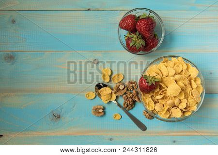 Tasty Cornflakes Wit Walnut And Strawberries In Glass Bowl On Blue Background. Top View. Corn Flakes