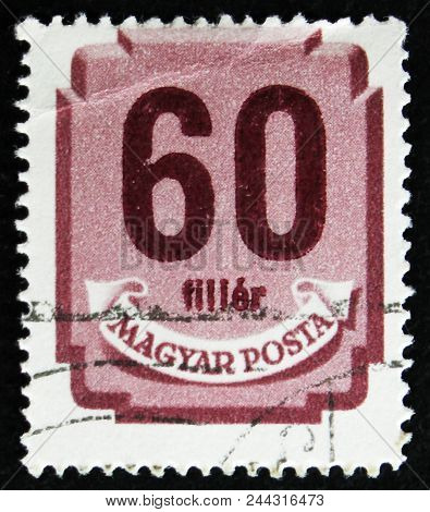 Moscow, Russia - April 2, 2017: A Post Stamp Printed In Hungary Shows Shield With Digits, Circa 1958
