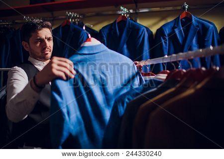 Tailor, Tailoring. Men's Suit, Tailor In His Workshop. Elegant Man's Suits Hanging In Row. Luxury Me