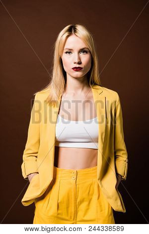 Portrait Of Stylish Blonde Girl In Yellow Clothes Standing With Hands In Pockets And Looking At Came
