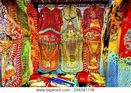 Blue Red Yellow Chinese Dragon Replica Silk Garments Robes Panjuan Flea Market  Decorations Beijing China.  Panjuan Flea Curio market has many fakes, replicas and copies of older Chinese products, many ancient. poster