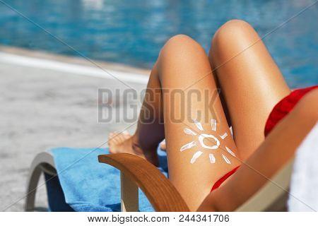 Young Woman With Sun Shape On The Leg Holding Sun Cream Bottle On The Beach. Sun Protection Sun Crea