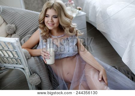 Pregnant Happy Smiling Woman Sitting On A Sofa And Caressing Her Belly. Mom Expecting Baby. Pregnant
