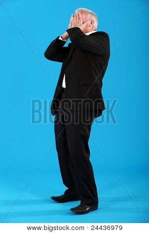Well-dressed man covering his face with his hands