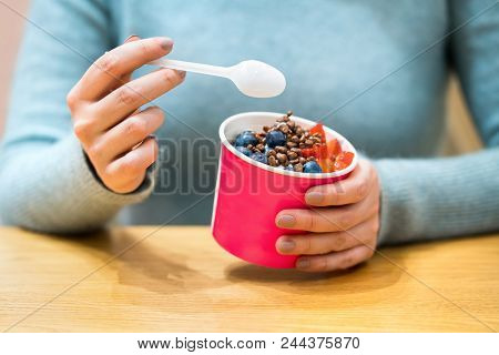 Frozen Yogurt Or Ice Cream With Toppings In A Cup. Woman Eating Frozen Yoghurt With Spoon.