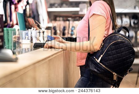 Woman At Checkout In Fashion Store Paying With Credit Card. Customer Using Payment Terminal Machine.