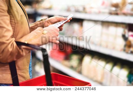 Woman In Supermarket Aisle With Food Shelf Reading Shopping List And Holding Basket. Woman Buying Gr