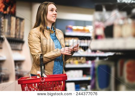 Woman With Shopping List In Supermarket And Grocery Store. Happy Customer Doing Groceries With Budge