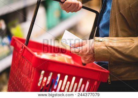 Hand Holding Shopping List And Basket In Grocery Store Aisle. Woman Reading Paper, Shelf In The Back