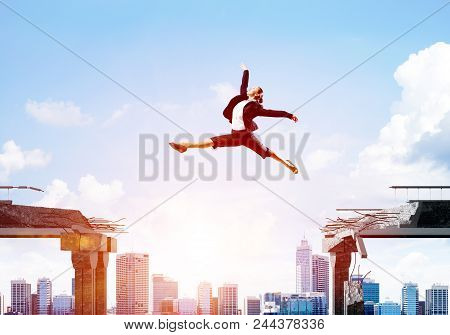 Business Woman Jumping Over Gap In Concrete Bridge As Symbol Of Overcoming Challenges. Cityscape Wit