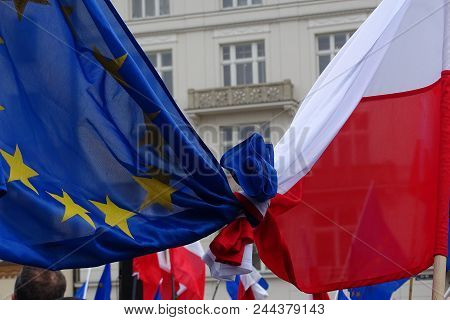 Flags Of Poland And European Union Tied Together During Street Demonstration, In Background Building