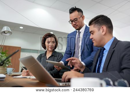 Multi-ethnic Team Of Financial Managers Analyzing Statistic Data With Help Of Digital Tablet While H