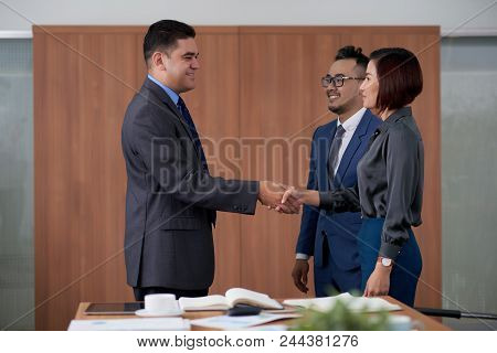 Profile View Of Smiling Middle-aged Entrepreneur Shaking Hand Of Pretty Business Partner After Succe
