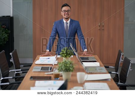 Asian Businessman Wearing Classical Suit Looking At Camera With Wide Smile While Standing At Modern