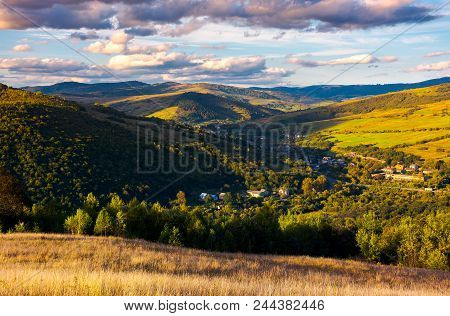 Beautiful Carpathian Countryside At Sunset. Village Down In The Valley In Shade Of A Nearby Mountain
