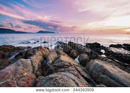 Long Exposure Image Of Dramatic Sky Seascape With Rock In Sunset Scenery Background