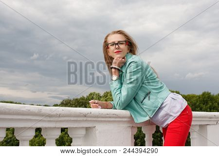 Smiling Girl In Glasses Standing Near Concrete Railing With Green Trees Background. Concept Of Archi
