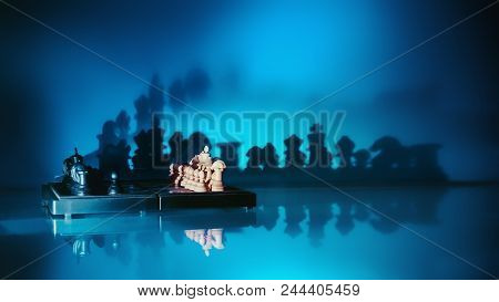 Chess Pieces On The Board Casting Increasing Shadows On A Blue Wall With Reflection. Conceptual Back