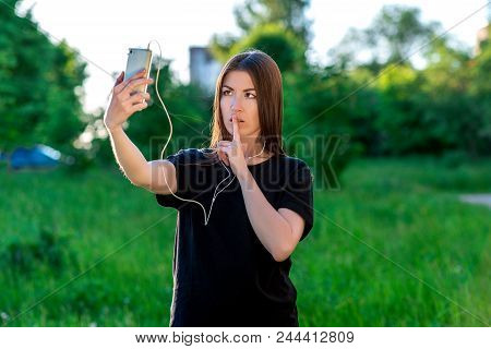 The Girl Is Talking On The Phone Video Call. Hold Your Hand With Your Lips. Show A Gesture. Do Not T