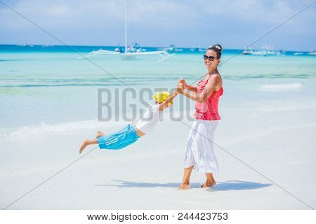 Happy Family Relaxing By The Sea. Happy Mother And Son Resting At Beach In Summer. Mother With Boy R