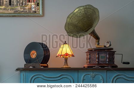 Nineteenth Century Phonograph (gramophone) And Vinyl Records On A Wooden Table And Background Of Bei