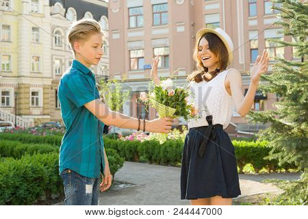 Romance In Couple Of Teens, Teenager Boy Surprises Gives Bouquet Of Flowers To His Girlfriend Outdoo