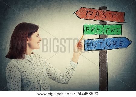Smiling Young Businesswoman Drawing A Signpost With Arrows That Shows Past, Present And Future. Lost
