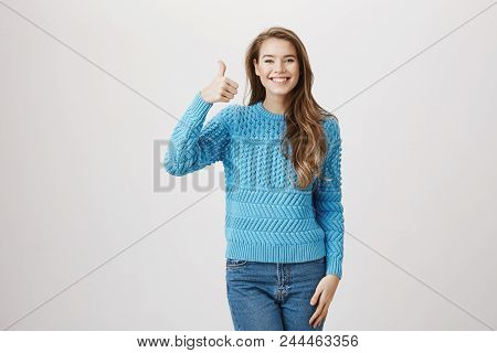 Positive Charming Young Adult Woman Raising Thumbs Up While Being Upbeat And Smiling Broadly At Came