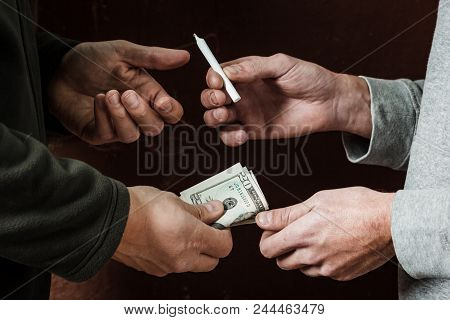Hand drug addict with money buys a dose of marijuana from a drug dealer. Concept of drug abuse and trafficking. poster