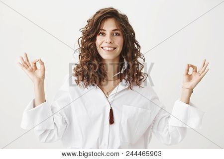 Positive Joyful Caucasian Adult Female With Curly Hair Smiling And Standing In Meditating Pose With