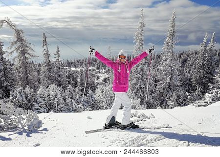 Young Woman In Pink Ski Jacket With Skis On Her Feet Holding Ski Poles Up, In Happy Pose Smiling On